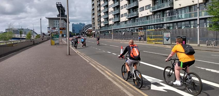 People cycling along a temporary cycle lane marked with cones