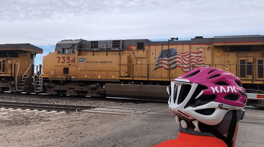 A view of a large yellow freight train with a stars and stripes flag rolling past
