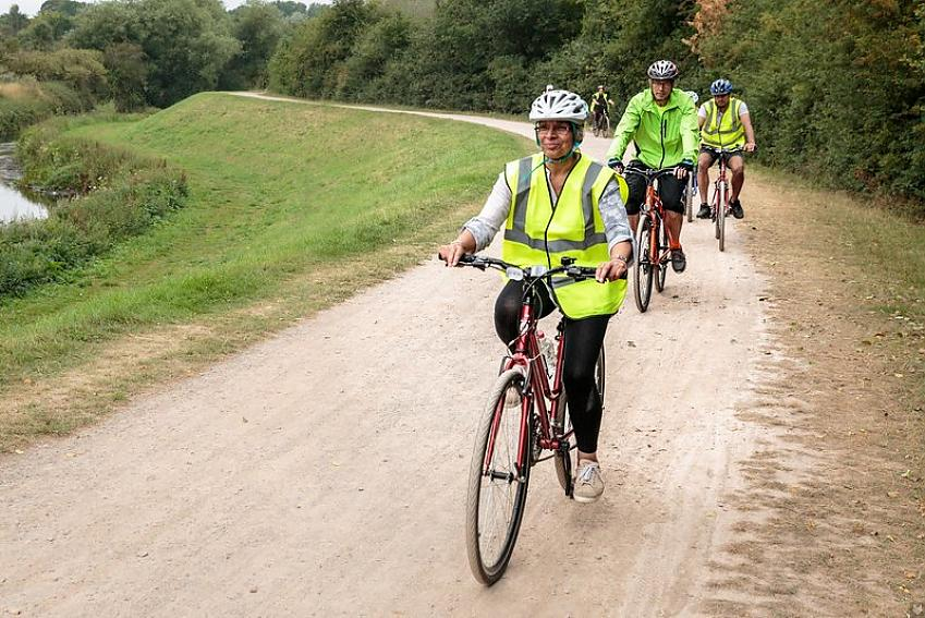 Two cyclists in yellow hi-vis riding an off-road path