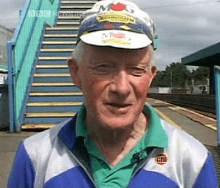 A close up of the face of a man with a cycling cap standing on a railway platform