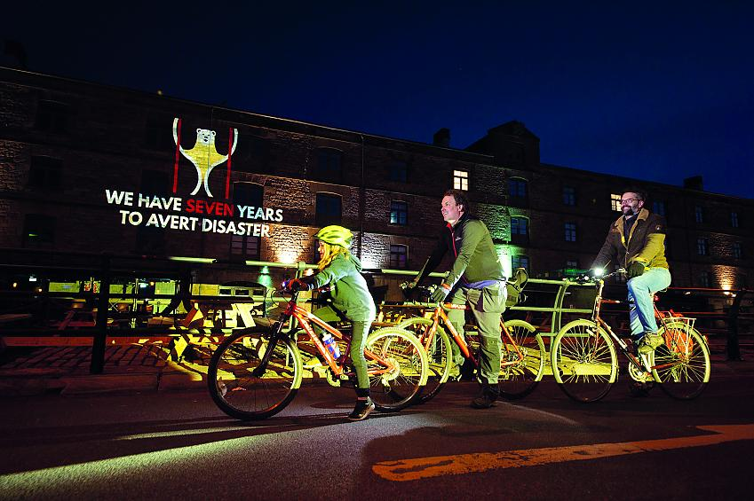 Two men and a young girl cycle on bikes in front of a lit up building