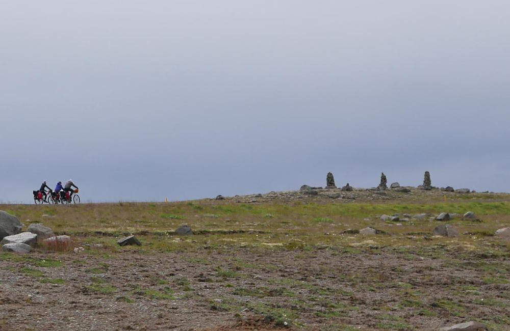 Cyclists riding past standing stones in Iceland