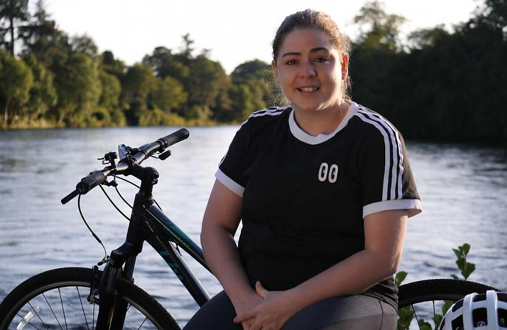 A young woman sat by a lake with her bicycle