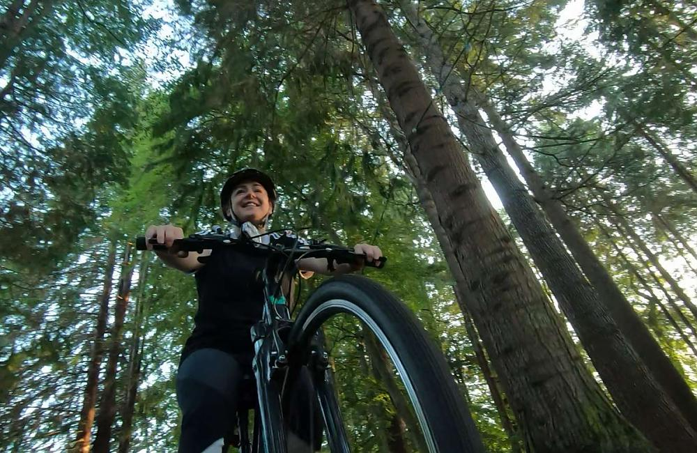 The camera looks up at a woman in dark clothing rides her bicycle through a woodland area