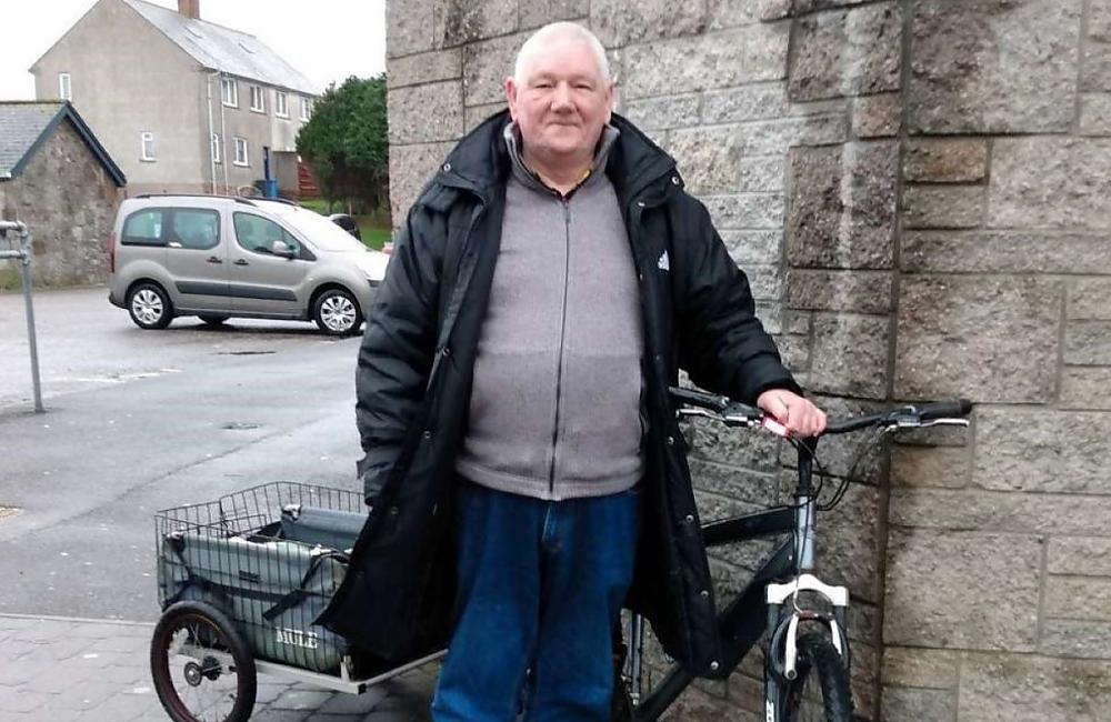 A man stands next to his bicycle which has a small trolley on the back