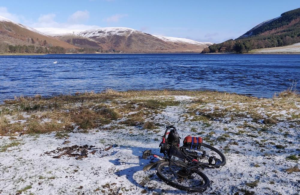 Bike resting in the snow in front of a loch