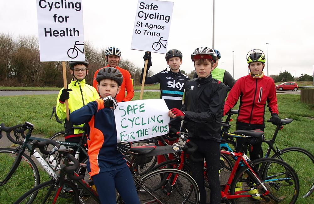 Group of young cyclists holding placards