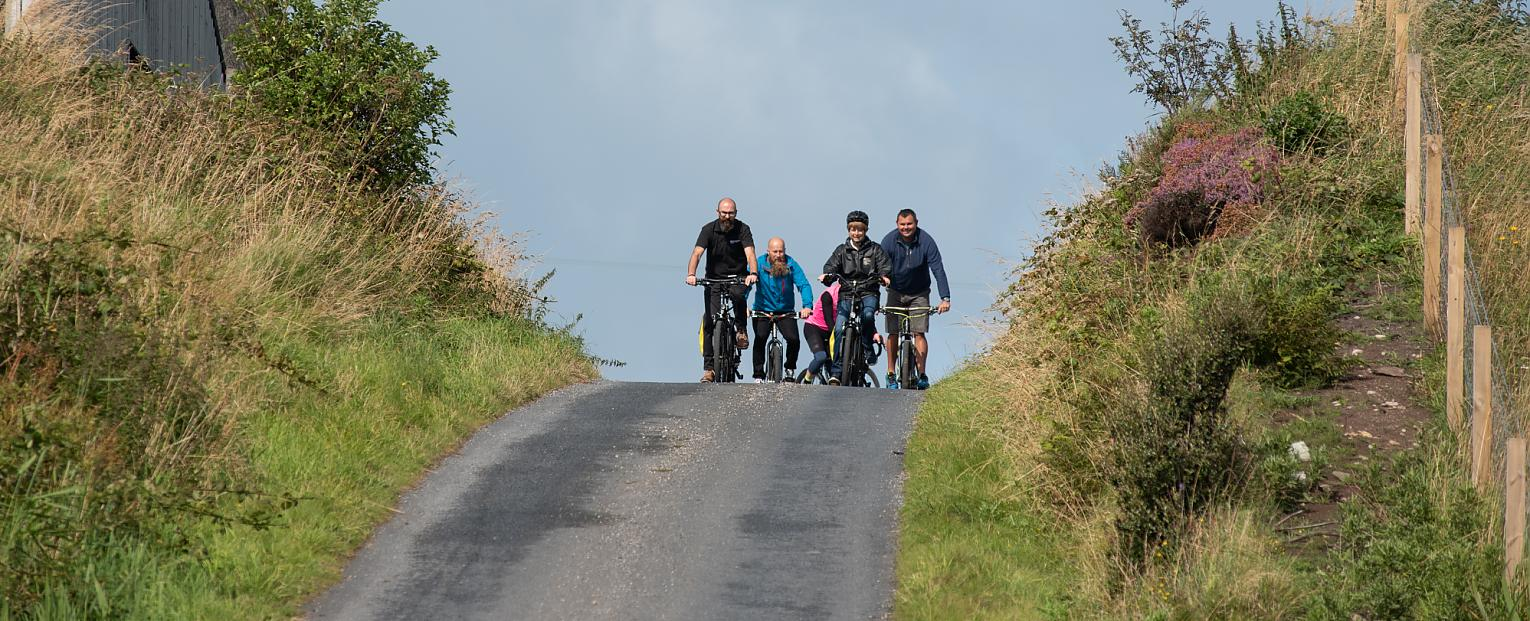 A group of cyclists in the distance riding towards the camera on a straight road.